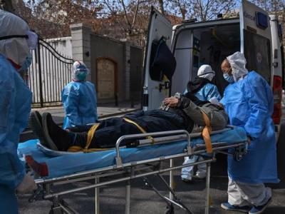 Medical staff in protective clothing carry a patient suspected of having the virus from an apartment in Wuhan, the capital of Hubei province. Some 242 people in Hubei died from the infection on Wednesday [Hector Retamal/AFP] - taken from Al Jazeera